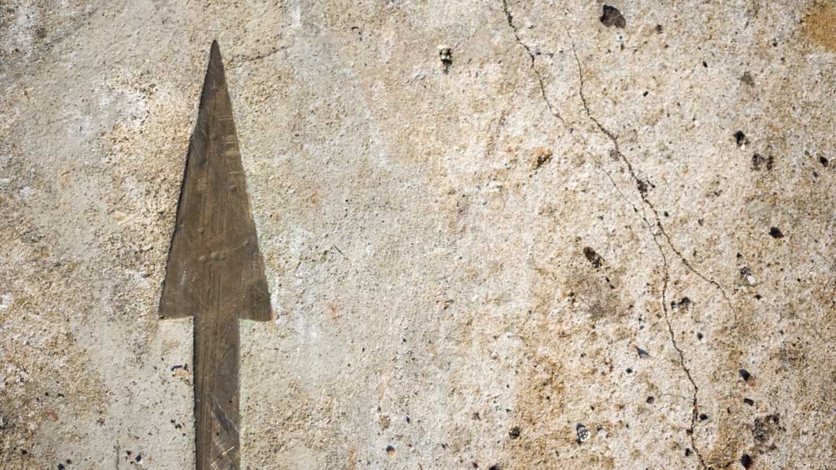 arrow etched on old stone wall
