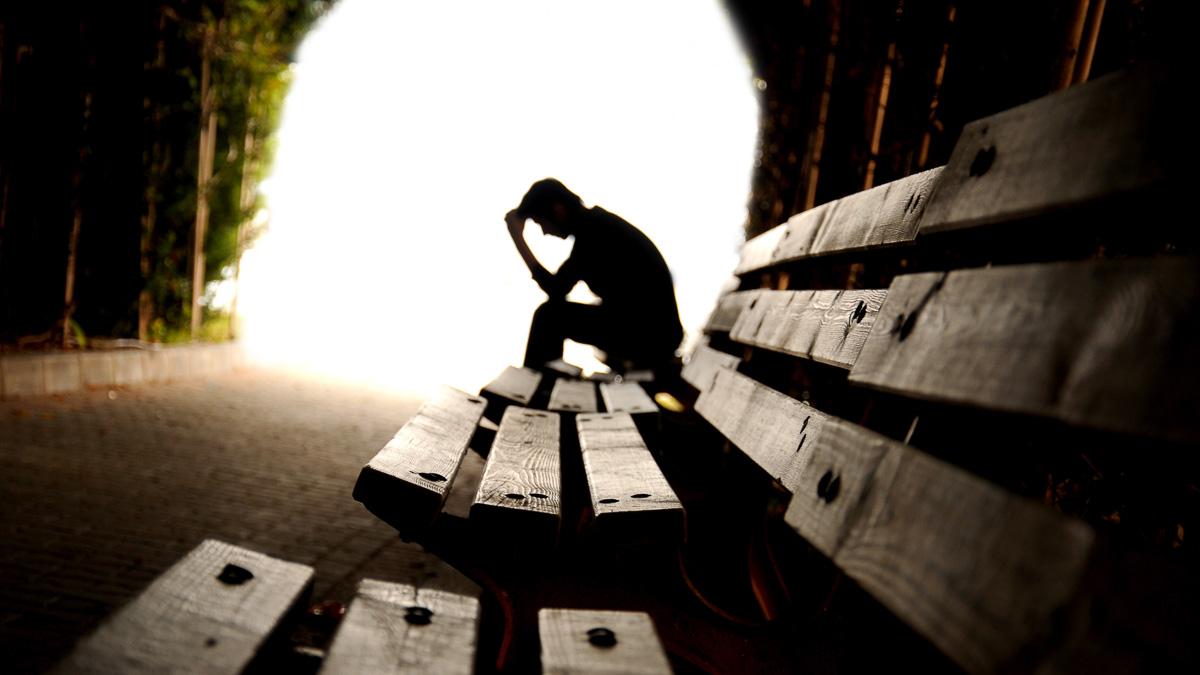 Siluett av deprimerad man som sitter på en bänk i en tunnel