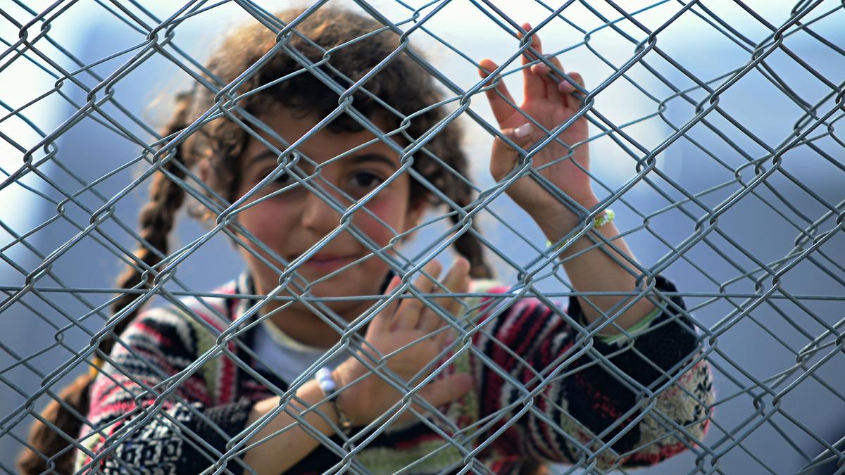 leende flicka som står bakom nät i flyktingläger