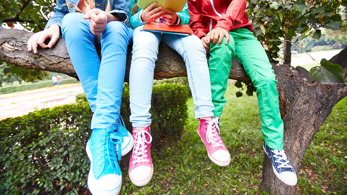 tre skolbarn som sitter i ett träd och läser