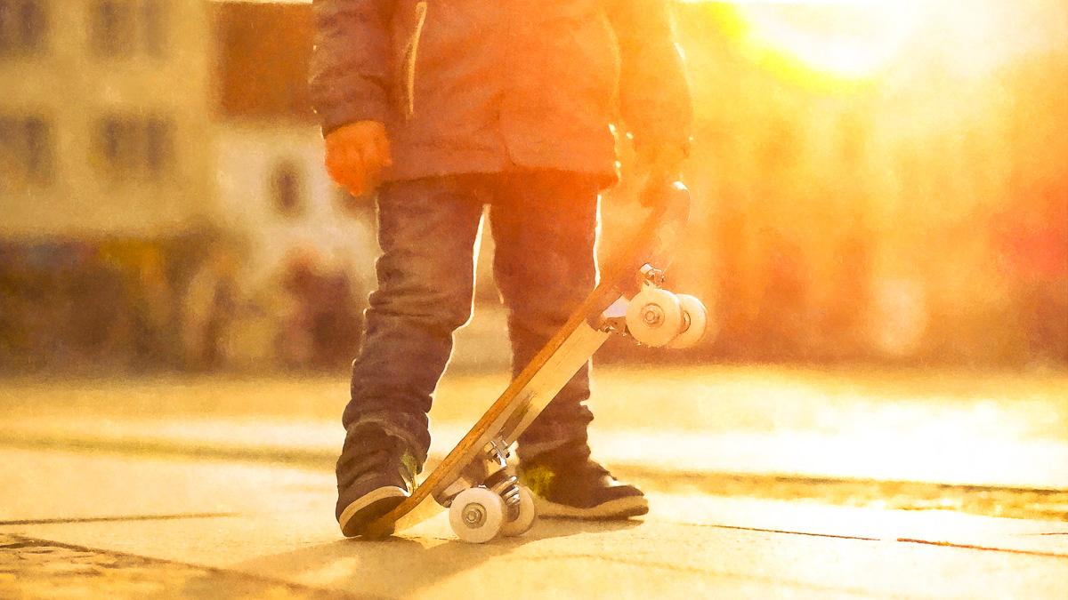 barn med skateboard, hus i bakgrunden, solnedgång