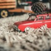 Toy car carrying christmas pine cone