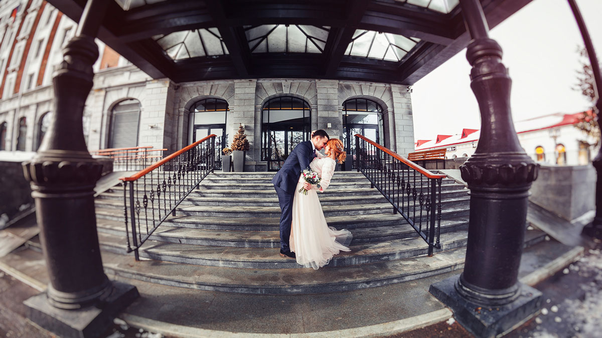 Bride and groom walking in the city. The picture on the wide-angle fisheye lens on the background of the modern hotel