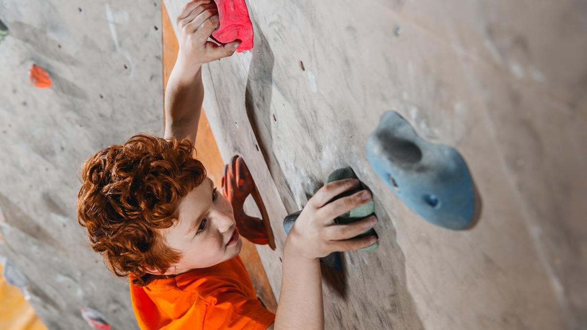 Barn klättrar upp för en klättervägg.