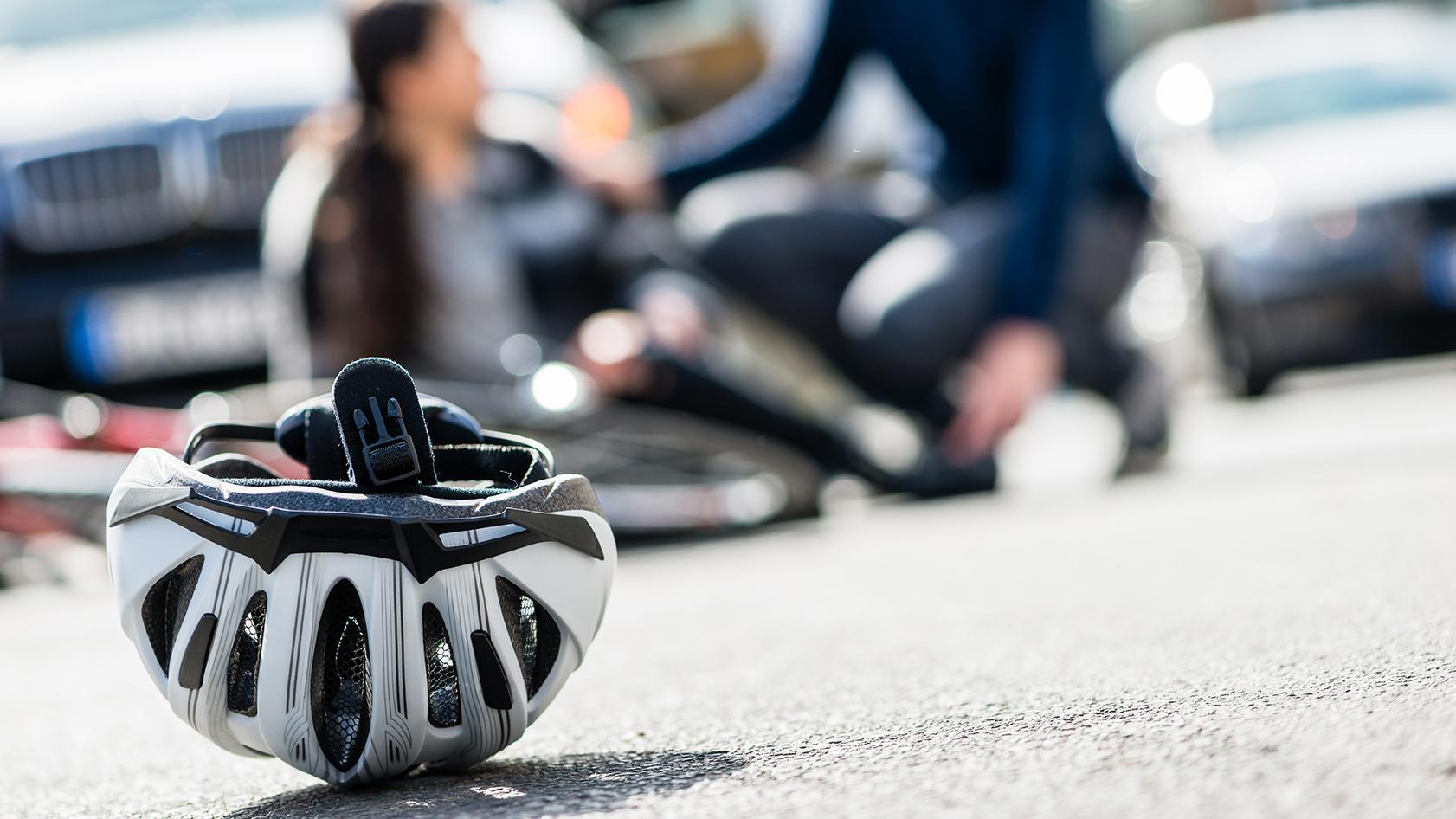 Cykelolycka. Kvinna har trillat på cykel. Cykelhjälmen ligger på marken.