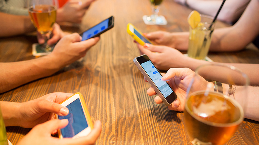 Händer håller i mobiltelefoner.