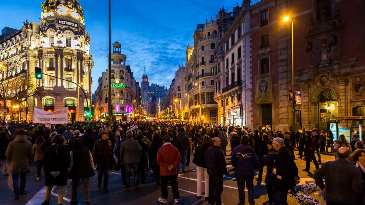 stor folksamling på gata i Madrid. Männiksor med baderoller och plakat med budskap mot bostadslöshet.