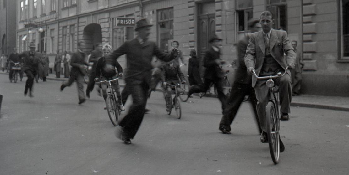 Människor springer och cyklar om varandra på en gata i Linköping.