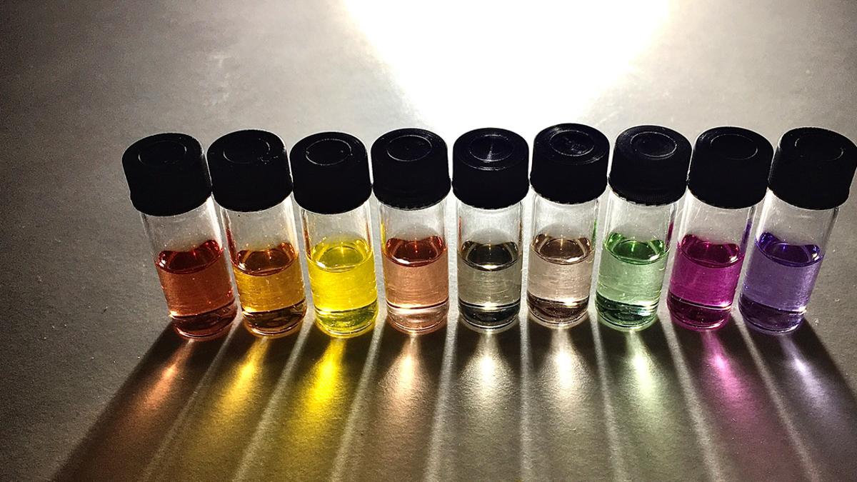 Nio små flaskor fyllda med vätska i olika färger.
