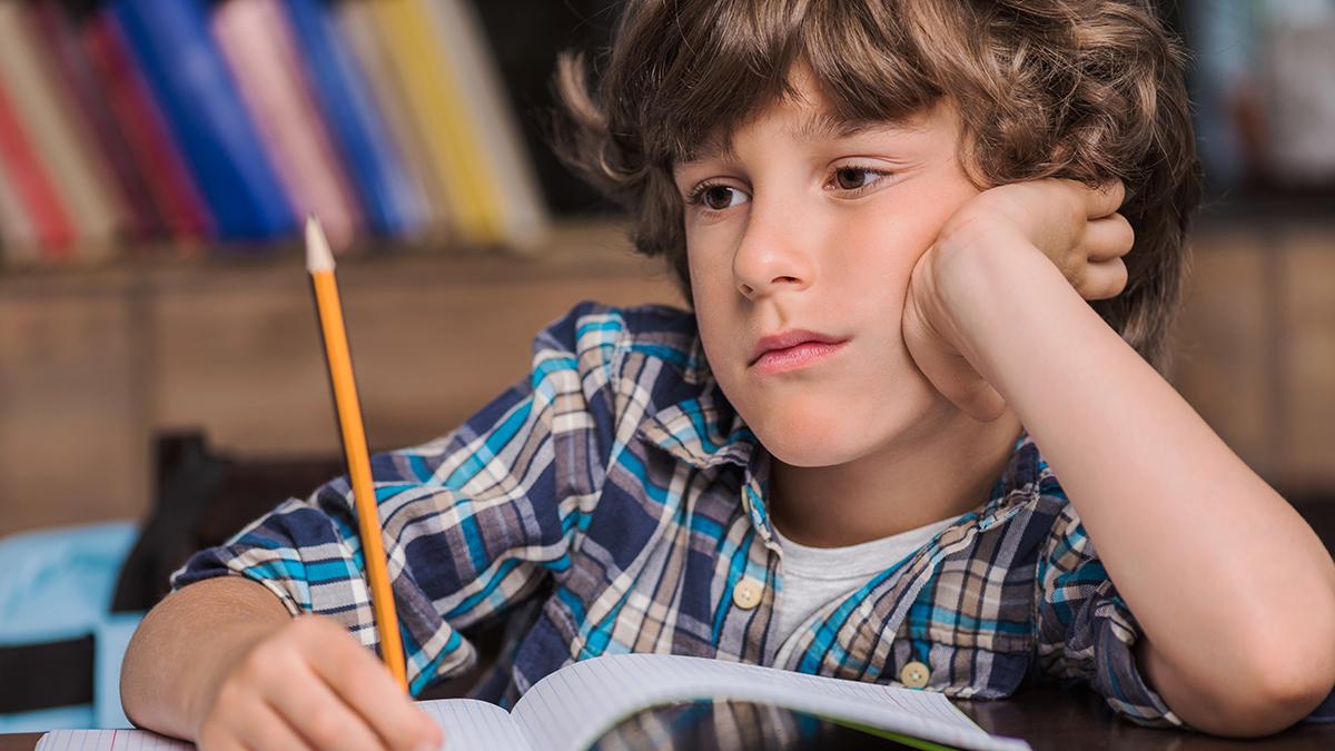 Barn i skolan som tittar tankfullt framför sig.