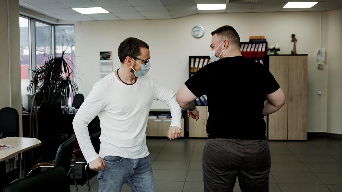 Två män hälsar på varandra med armbågarna, en coronahälsning.