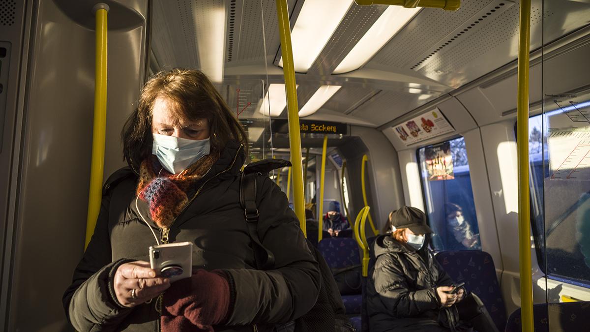 Kvinna åker buss med munskydd under coronapandemin och tittar på sin mobil.