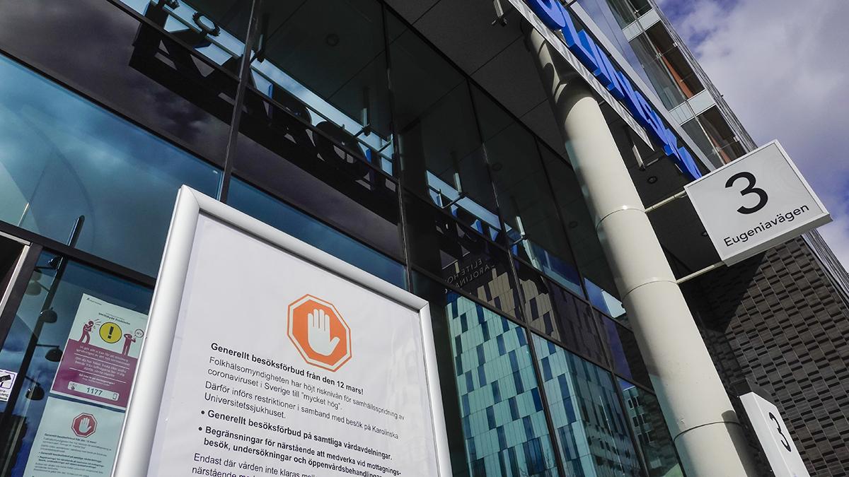 Entrén till Karolinska sjukhuset med skylt som hänvisar till besöksförbud med anledning av coronaviruset.