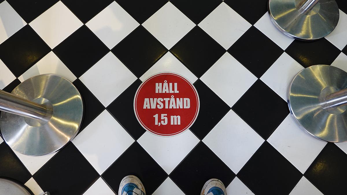 Klistermärke på golvet i en restaurang uppmanar besökare att hålla avstånd.
