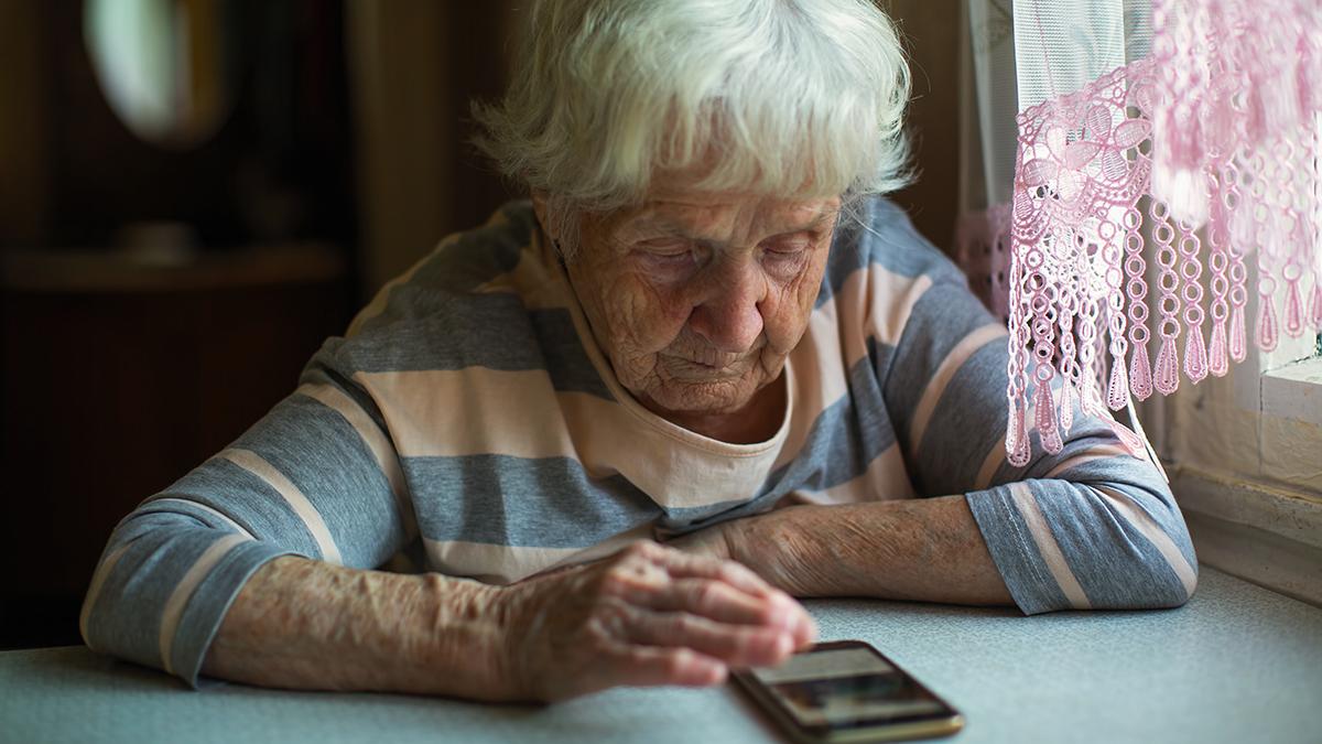 Äldre kvinna som tittar på sin mobiltelefon som ligger på bordet framför henne.