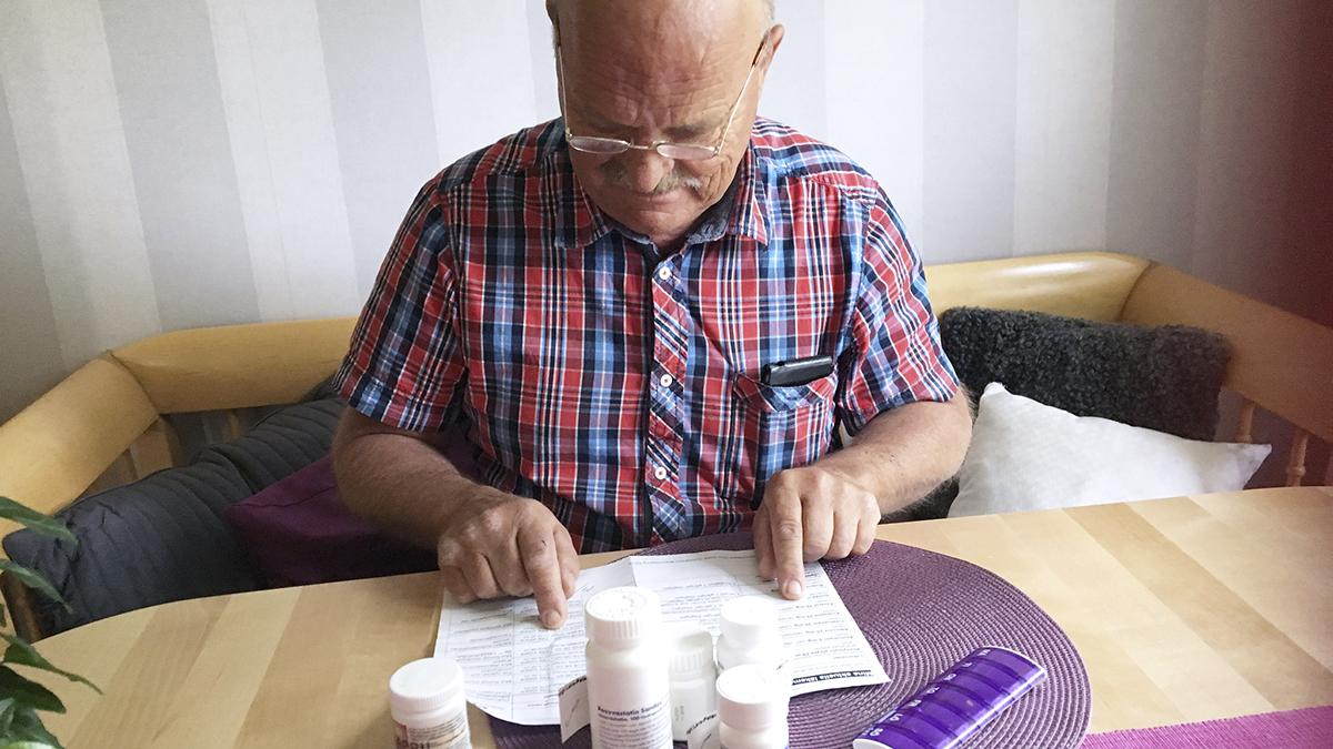 Man som går igenom sitt recept. På bordet står ett antal läkemedel.