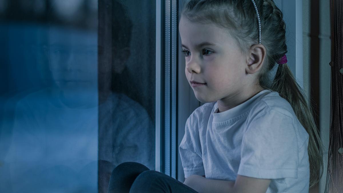 Ensam flicka sitter vid ett fönster.