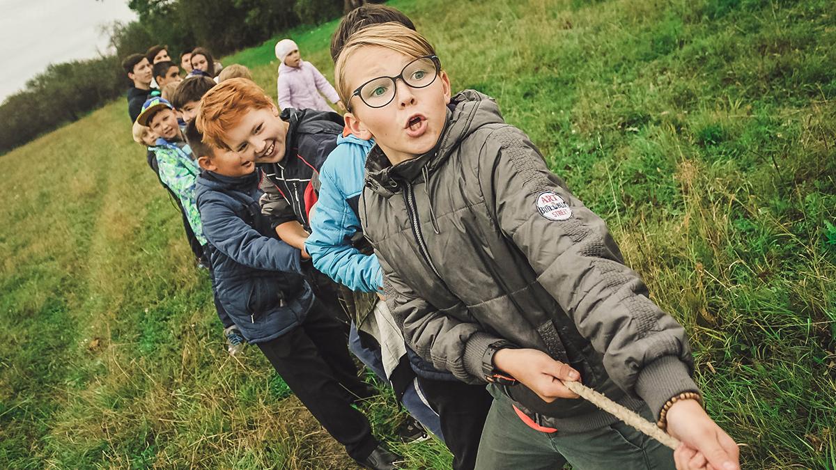 Barn i skolan som har dragkamp på en gräsmatta.