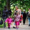 Personer från olika länder promenerar på en lummig grusväg