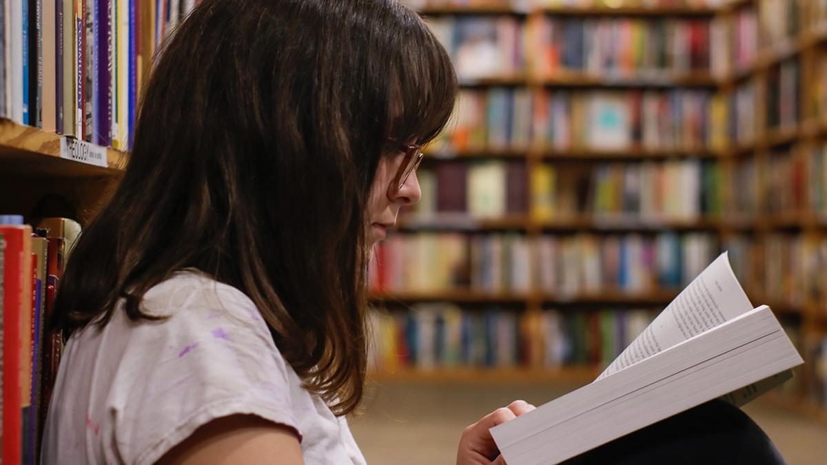 Elev som sitter på golvet och läser i skolans bibliotek.