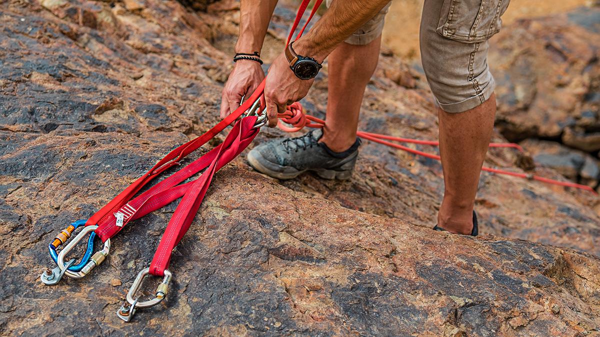 Benen på en man som bergsklättrar och använder utrustning för att förebygga olyckor.