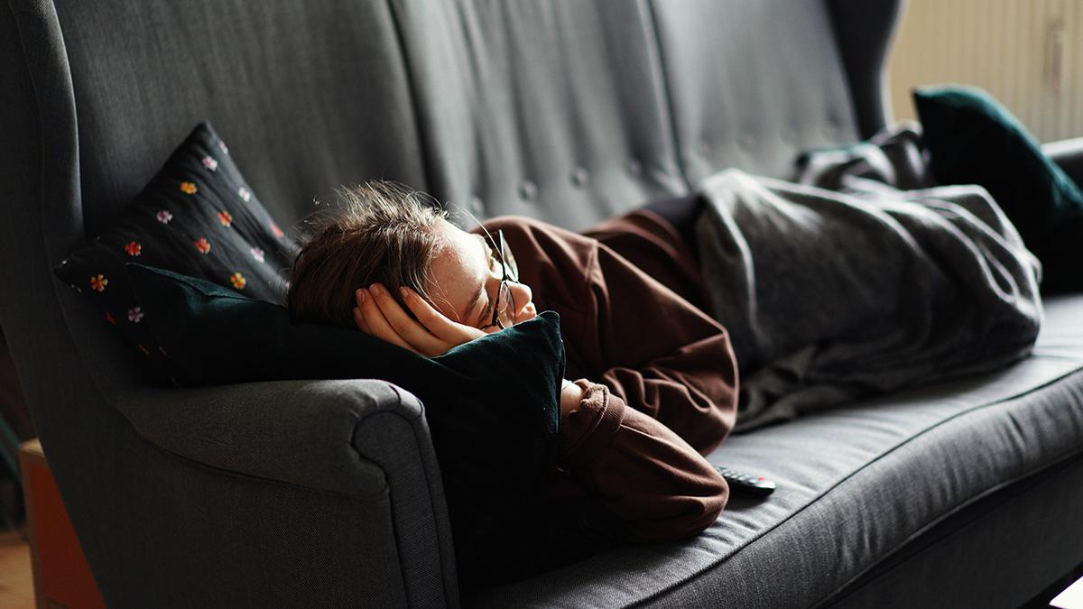 En människa ligger i en soffa under en filt och kollar på tv eller film.