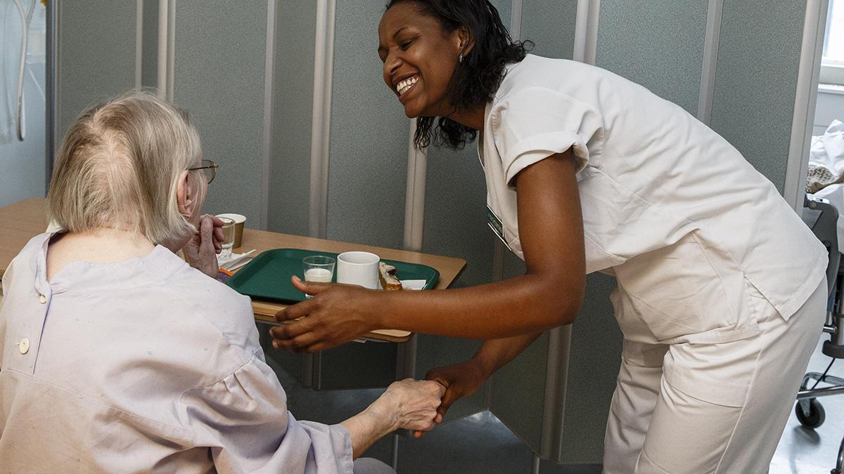 Sjuksköterska tillsammans med äldre kvinna på ett äldreboende.