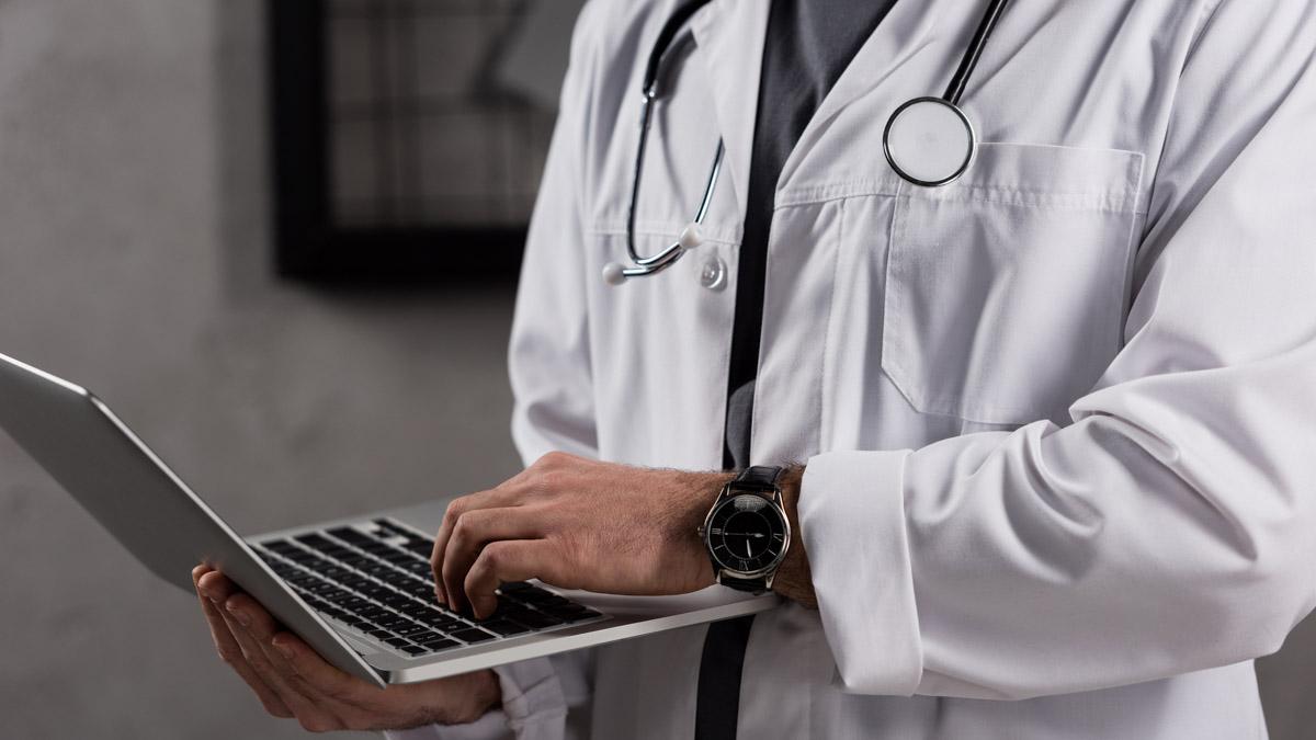 Nätläkare som håller i sin bärbara dator.
