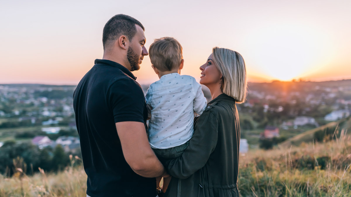 En pappa och mamma håller sitt barn i famnen.