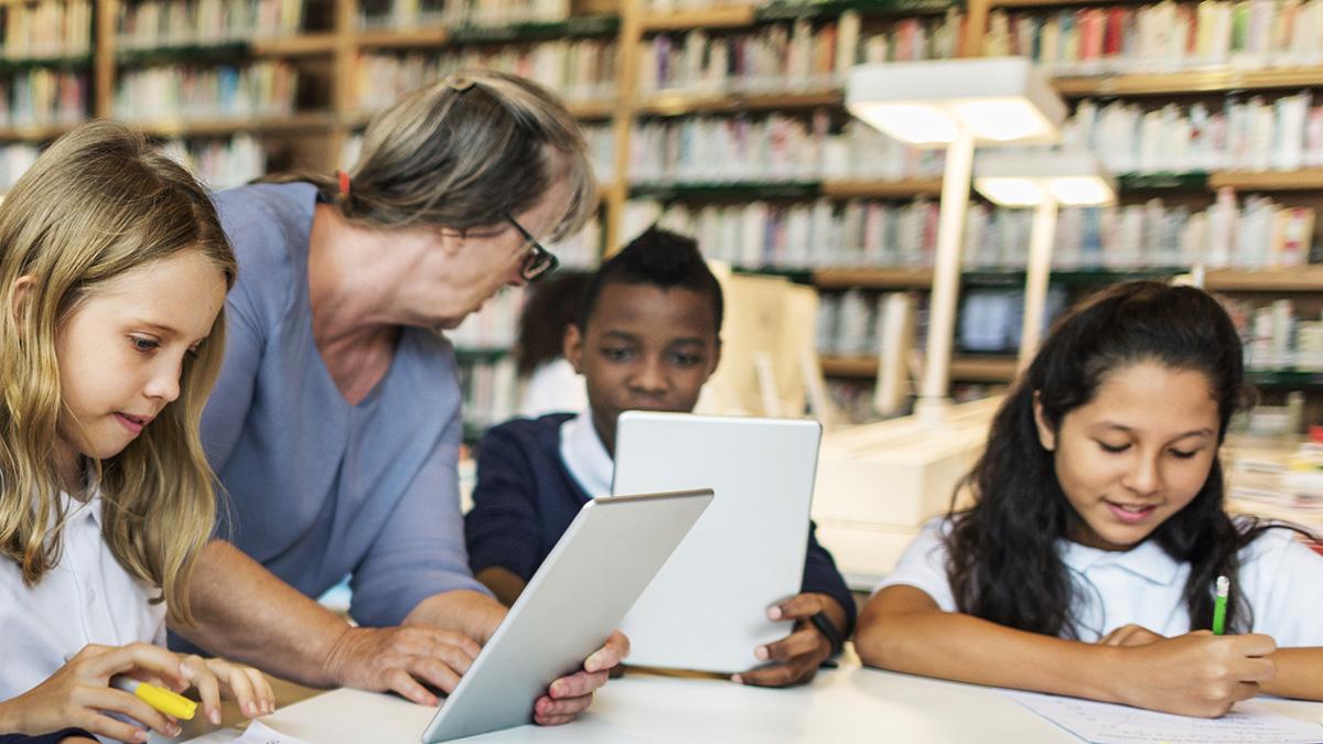 Barn läser på ipads i skolan.