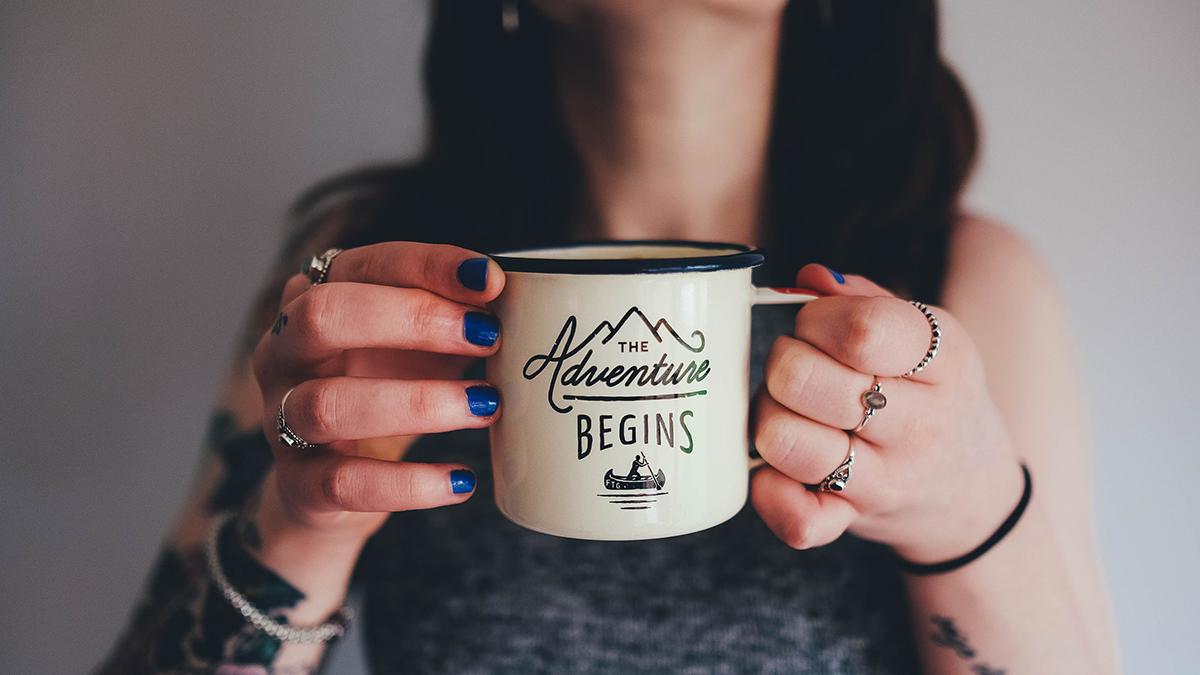"""Kvinna som håller i en kaffekopp med texten The adventure begins""""."""