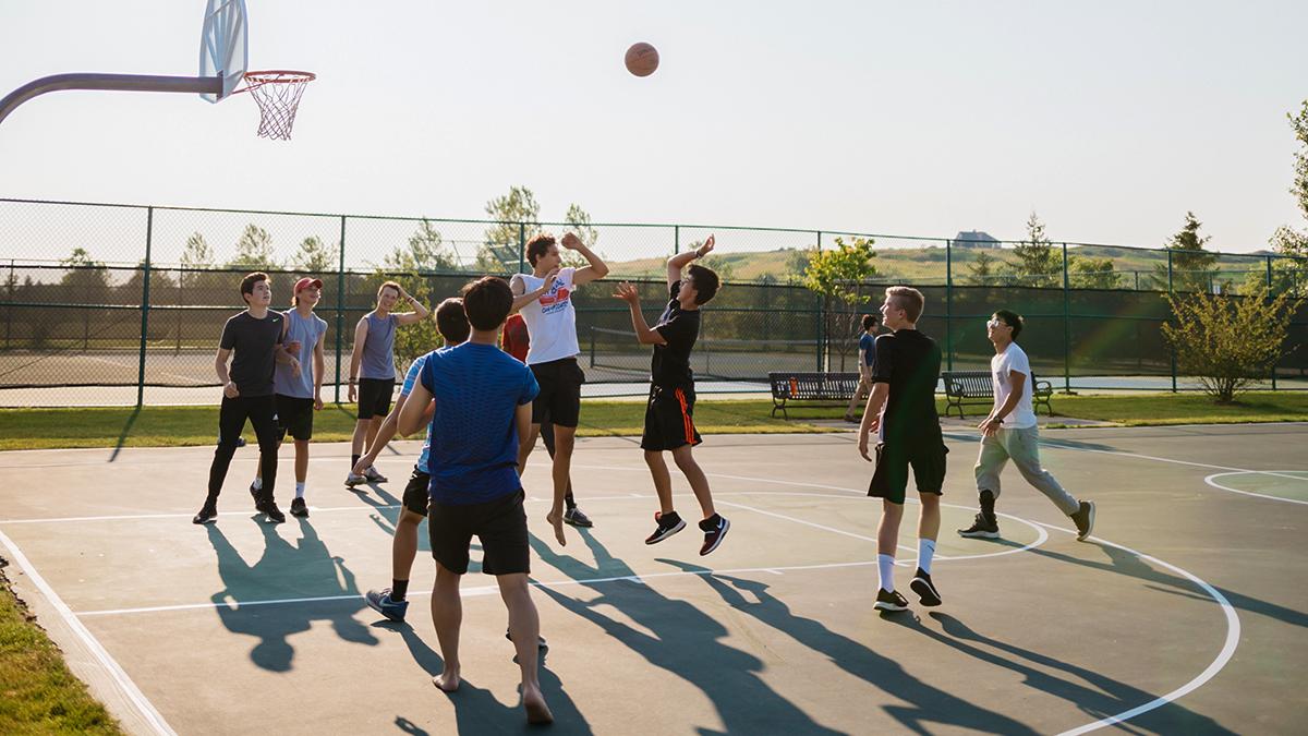 Tonåringar spelar basket.