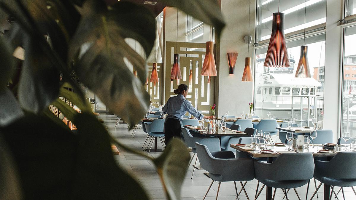 Servitör dukar bord på en restaurang.