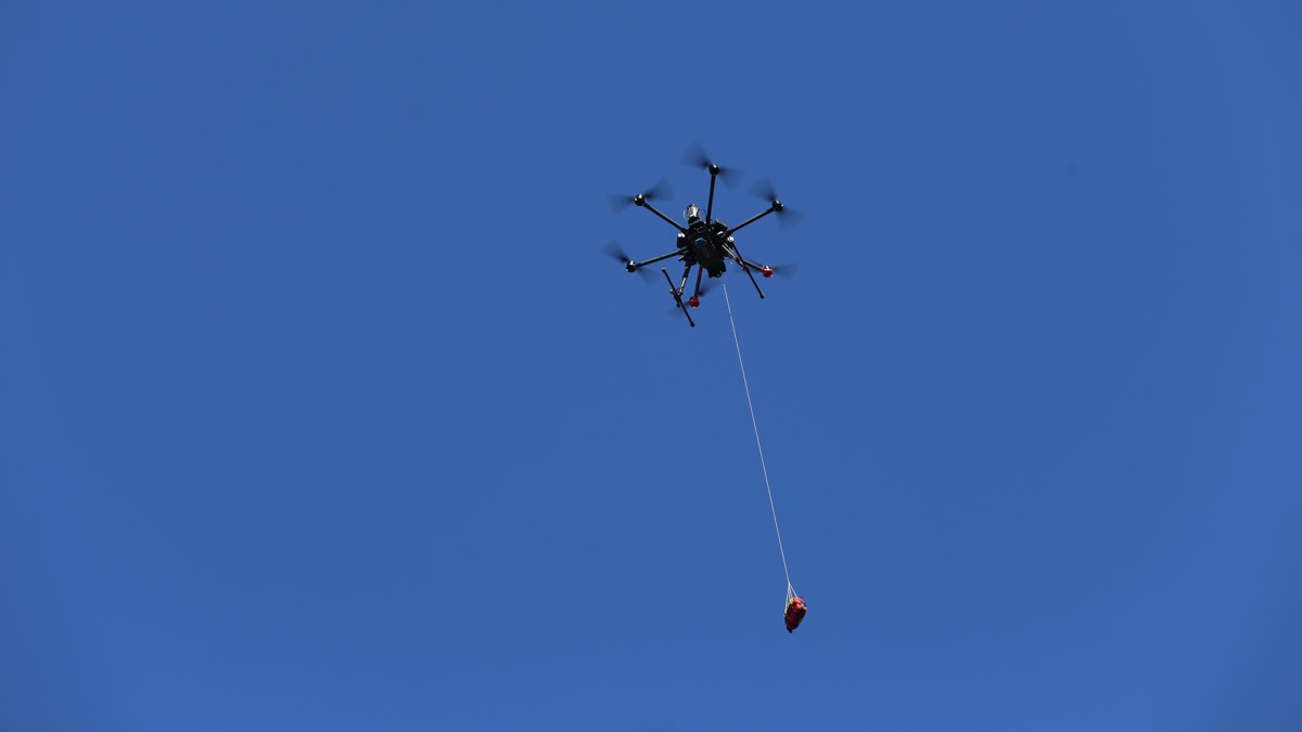 Drönare flyger med hjärtstartare fäst i rep.