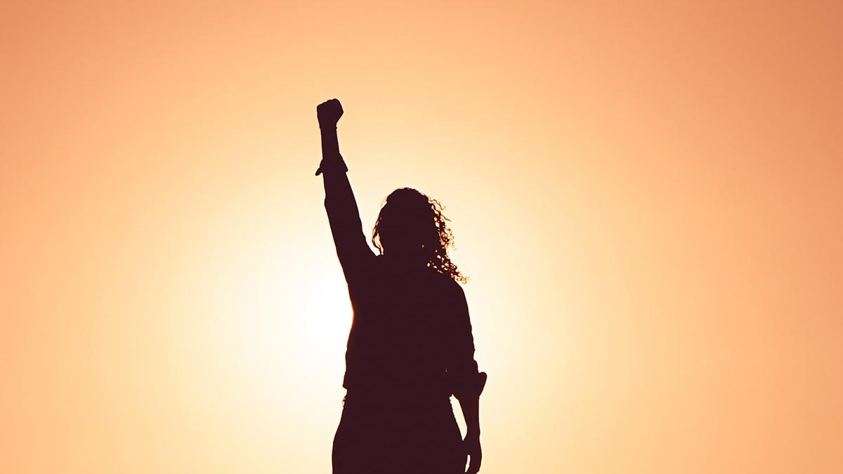 Silhuetten av en kvinna med knuten hand sträckt upp i luften, mot orange himmel.