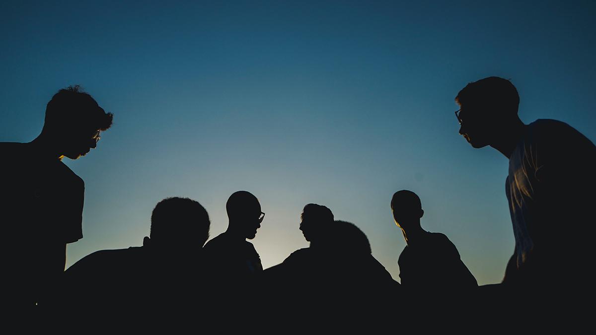 En grupp män avbildas som silhuetter mot en mörk himmel.