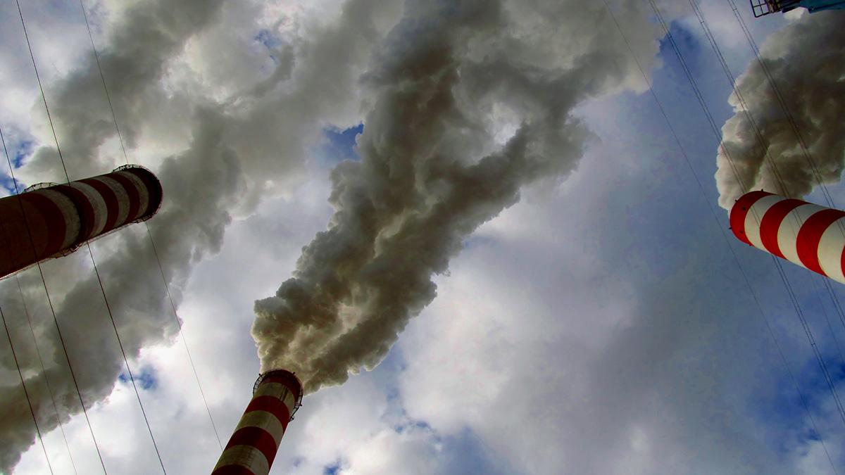 Tre industriskorstenar som släpper ut rök.